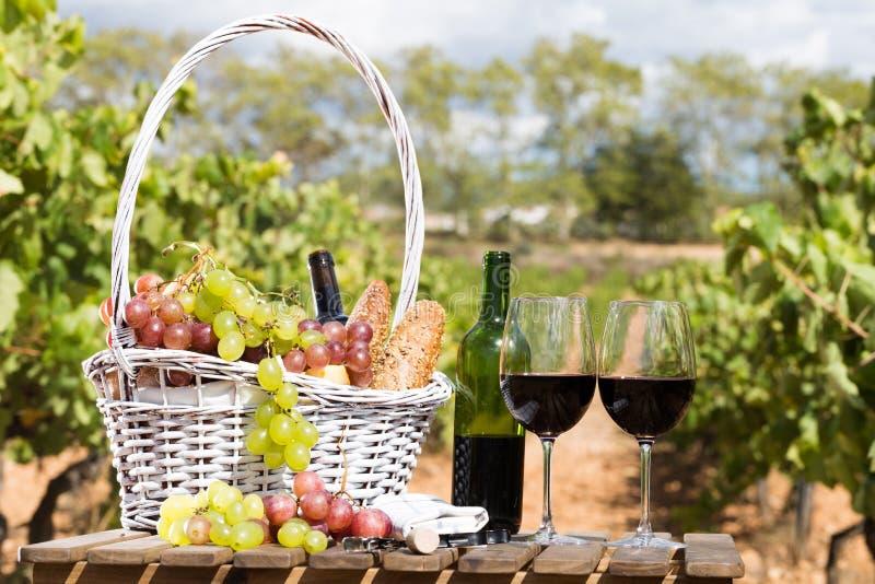 Stilleven met glas van rode wijndruiven en picknickmand op lijst royalty-vrije stock foto's