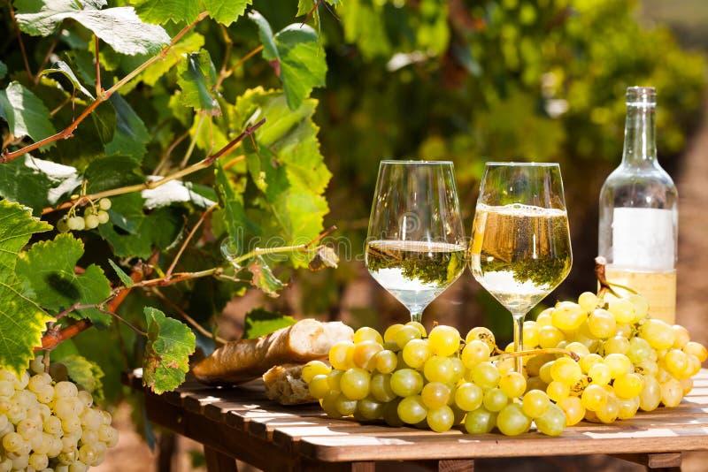 Stilleven met glas Wit wijndruiven en brood op lijst op gebied stock afbeelding