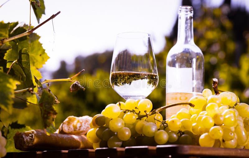 Stilleven met glas Wit wijndruiven en brood op lijst op gebied stock foto's