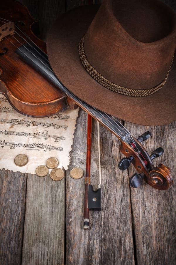 Stilleven met hoed, viool en muntstukken stock foto