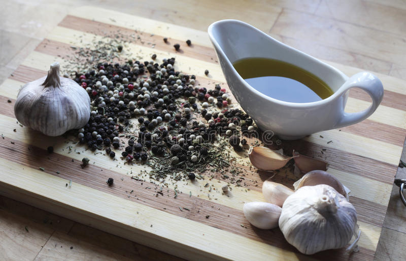 Stilleven met kruiden, knoflook, peper en olijfolie stock afbeelding