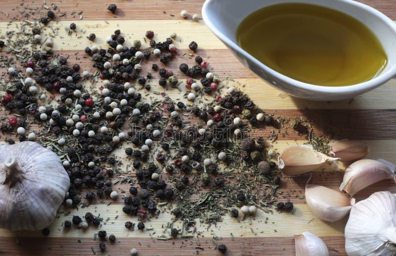 Stilleven met kruiden, knoflook, peper en olijfolie stock afbeeldingen