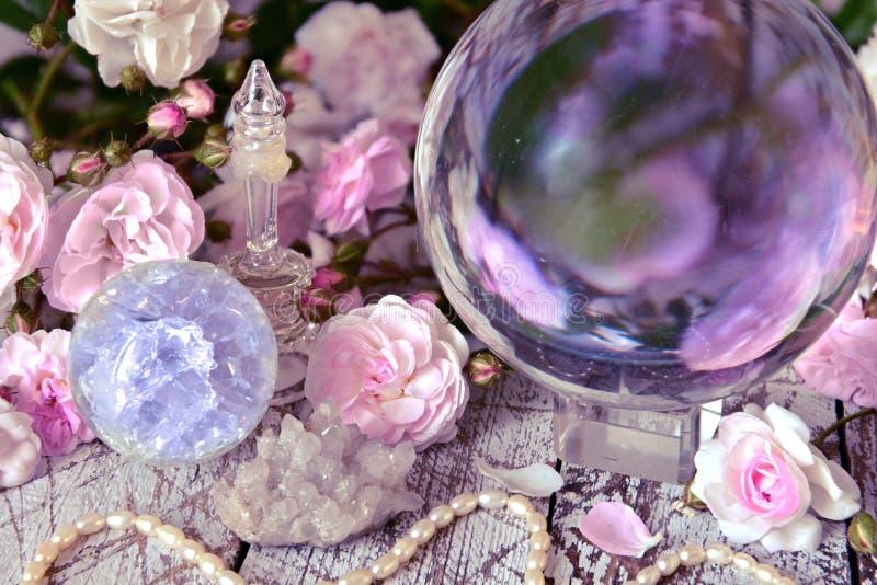 Stilleven met magische kristallen bol, roze rozen en halsband stock foto's