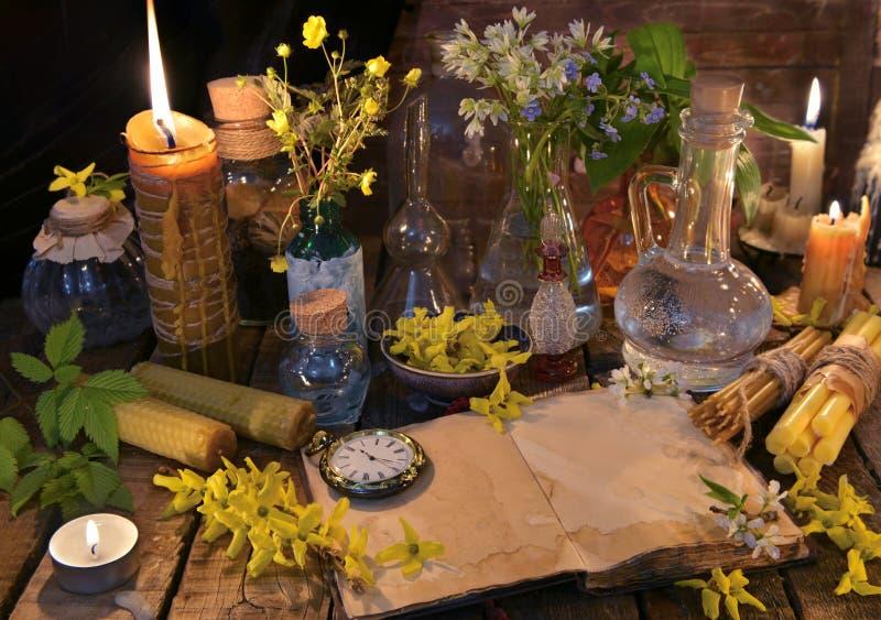 Stilleven met oude boek, kaarsen, glasflessen en het helen kruiden royalty-vrije stock afbeelding