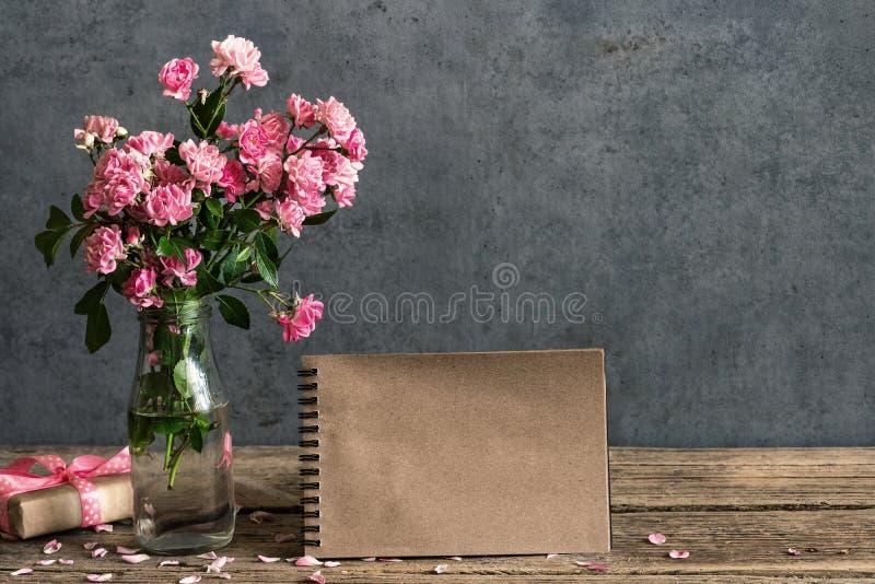 Stilleven met roze roze bloemenboeket, leeg document kaart en giftvakje Spot omhoog Het uitstekende stemmen royalty-vrije stock afbeeldingen