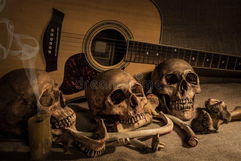Stilleven met schedel drie en beenderen over gitaarachtergrond royalty-vrije stock afbeeldingen