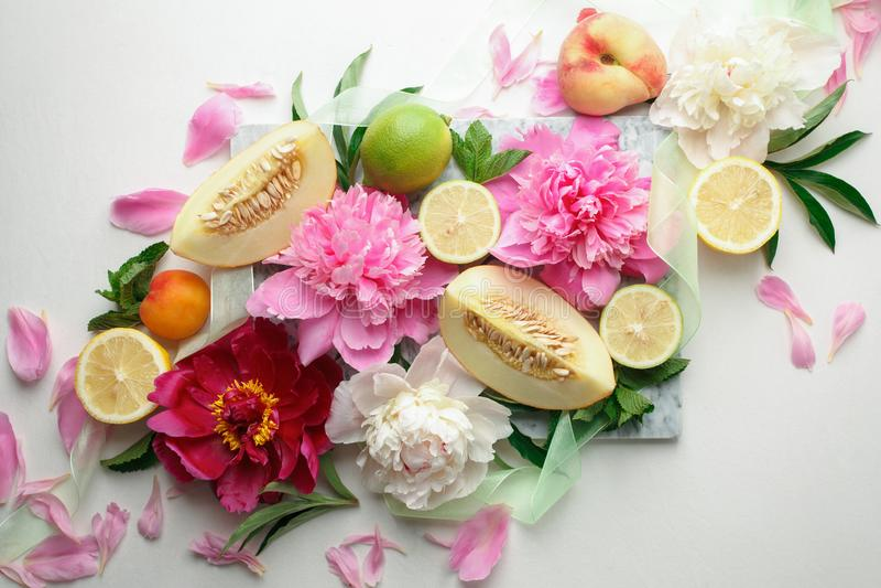 Stilleven met verse geassorteerde exotische vruchten en pioenbloemen op witte achtergrond Concept het gezonde eten met vruchten e stock afbeeldingen