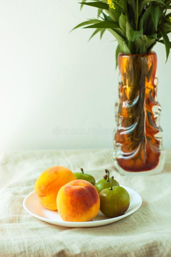 Stilleven met verse perziken en pruimen op de achtergrond van de linnendoek op houten lijst Heldere sappige de zomervruchten royalty-vrije stock afbeelding