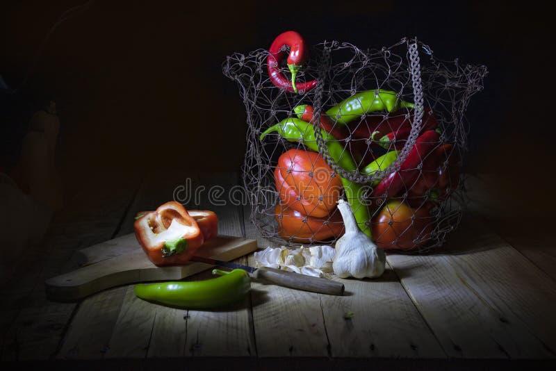 Stilleven op een zwarte achtergrond Spaanse peper, pompoen, Spaanse peperspeper en knoflook De peperhelften die op een hakbord li royalty-vrije stock afbeeldingen