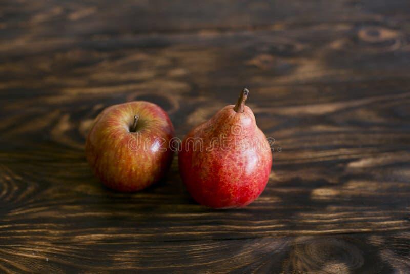 Stilleven 1 Peer en appel op een bruine achtergrond, op een scherpe raad stock afbeeldingen