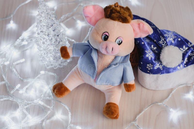 Stilleven roze gelukkige biggetje en LEIDENE vakantieslinger op houten achtergrond, gelukkig nieuw jaar stock foto's