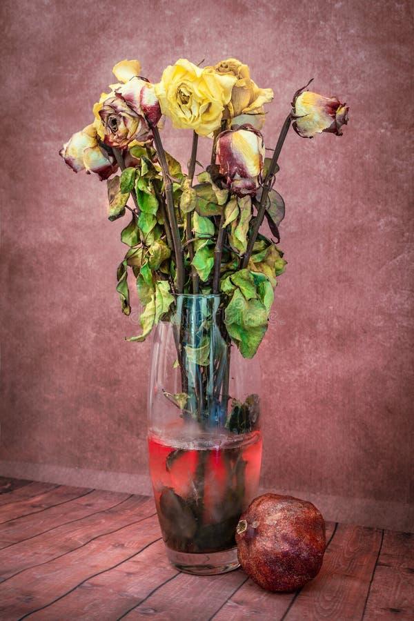 Stilleven van droge bloemen in een vaas met het water met granaatappel royalty-vrije stock foto's
