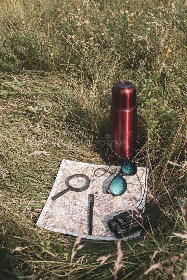 Stilleven van een reiziger Kaart, meer magnifier, verrekijkers, pen, glazen en een thermosfles in het gras stock afbeelding