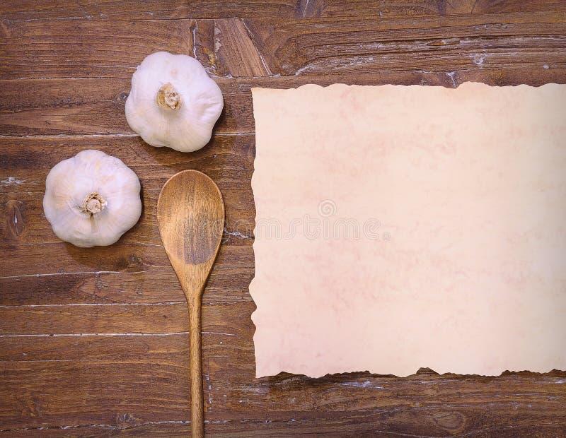 Stilleven van knoflook, lepel en bakseldocument op houten lijst stock afbeeldingen