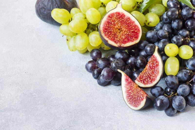 Stilleven van vers de herfstfruit Zwart en groene druiven, fig. en bladeren op een grijze lijst met exemplaarruimte stock fotografie