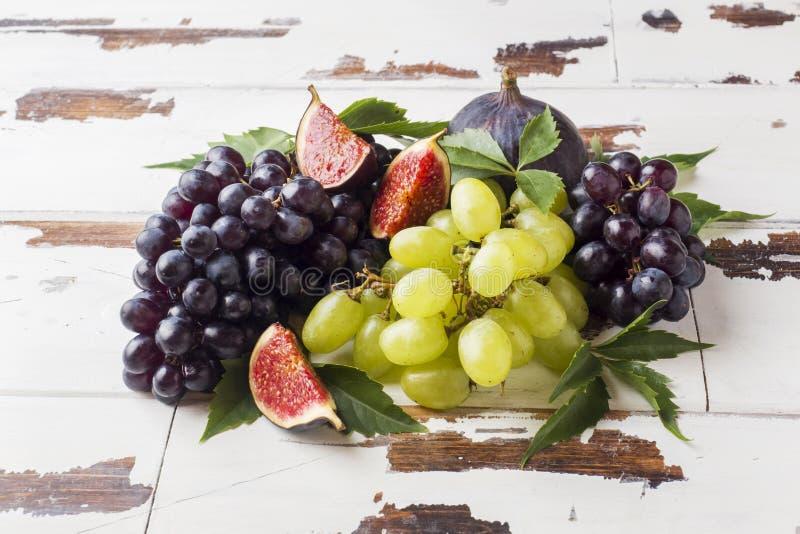 Stilleven van vers de herfstfruit Zwart en groene druiven, fig. en bladeren op een houten lijst met exemplaarruimte stock afbeelding