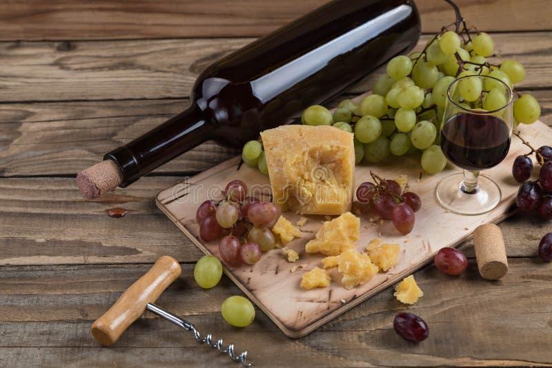 Stilleven van voedsel en wijn Het stuk van harde kaas ligt op een hakbord Clusters van rode en groene rijpe druiven, dark royalty-vrije stock foto's