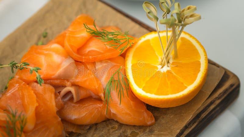 Stilleven van zalm en besnoeiing in halve sinaasappel op houten plaat stock foto