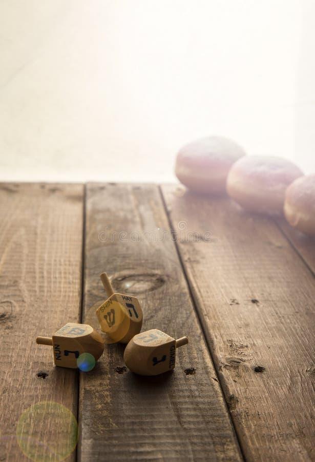 Stilleven voor Joodse vakantiechanoeka met 3 donuts en 3 dreidels op houten rustieke lijst Het concept van de Chanoekaviering Len royalty-vrije stock foto