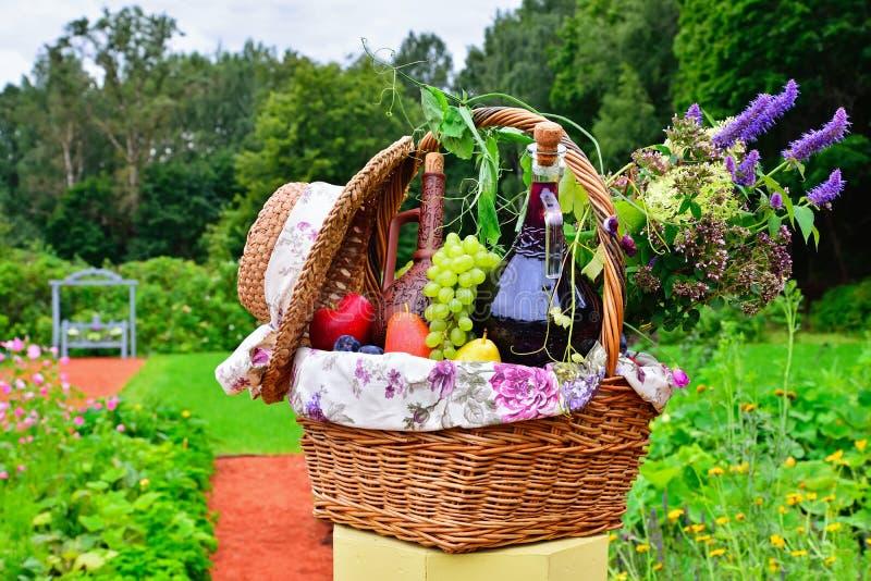 Stilleven: wijn, druiven, bloemen en groenten in de mand o stock afbeeldingen