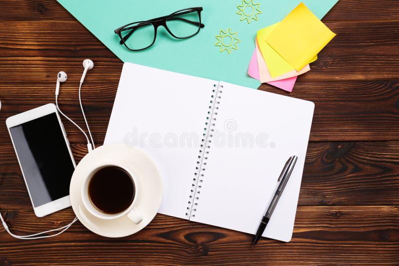 Stilleven, zaken, bureaulevering of onderwijsconcept: Hoogste mening van werkend bureau met leeg notitieboekje met potlood, koffi stock foto