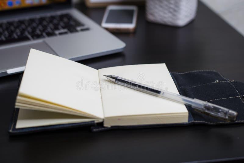 Stilleven, zaken, bureaulevering of onderwijsconcept: Hoogste meningsbeeld van open notitieboekje met blanco pagina's en laptope  royalty-vrije stock foto's