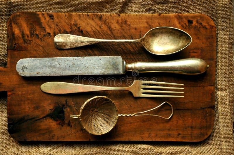 Stillevenbeeld met oude lepel, mes, vork en zeef stock foto