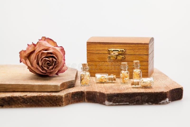 Stillevensamenstelling met houten vakje, kleine glasflessen met gouden document stock foto's
