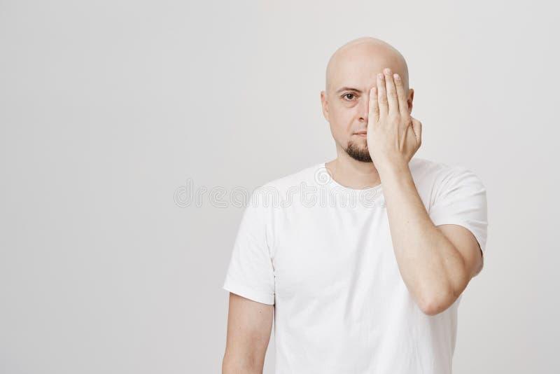 Stillhet och allvarlig skallig man med täckande halva för skägg av framsidan med handen, den bärande vita t-skjortan och anseende royaltyfri bild