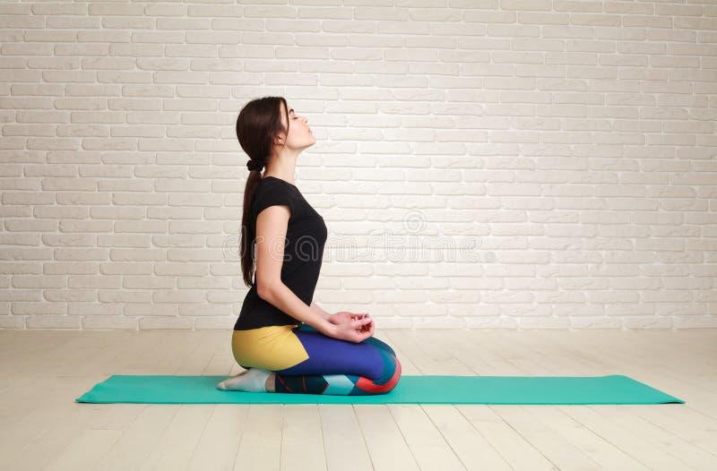 Stillhet och den koncentrerade kvinnan som gör yogaövningar i lotusblomma, poserar fotografering för bildbyråer