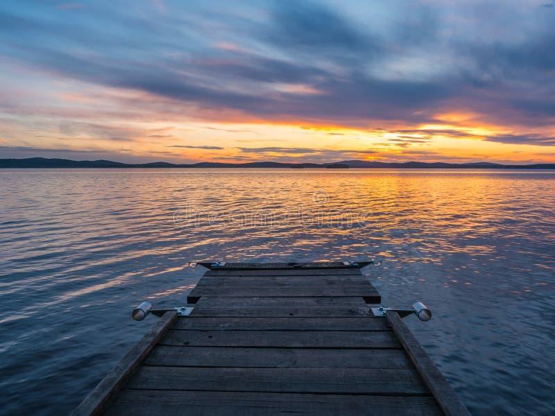 Stillhet- och meditationbegrepp Solnedg?ng p? sj?n, tr?bro i f?rgrunden, tyst vatten, molnfri himmel bl? timme royaltyfri foto