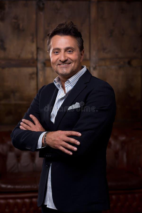 Stillhetaffärsman som ler, medan stå med hans armar korsade royaltyfri foto