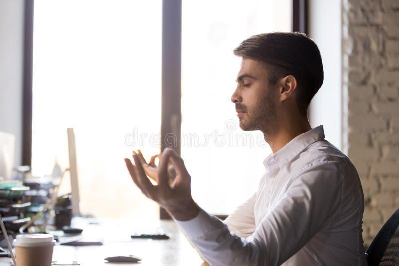 Stillhetaffärsman som sitter på kontorsskrivbordet som tar avbrottet för meditat arkivbilder
