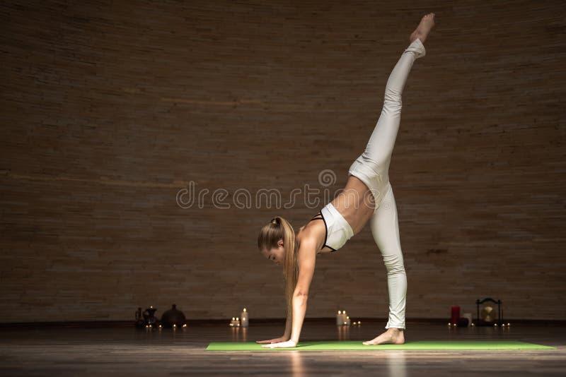Stillhetdam som sätter upp ett ben, medan öva ny yoga posera royaltyfri bild