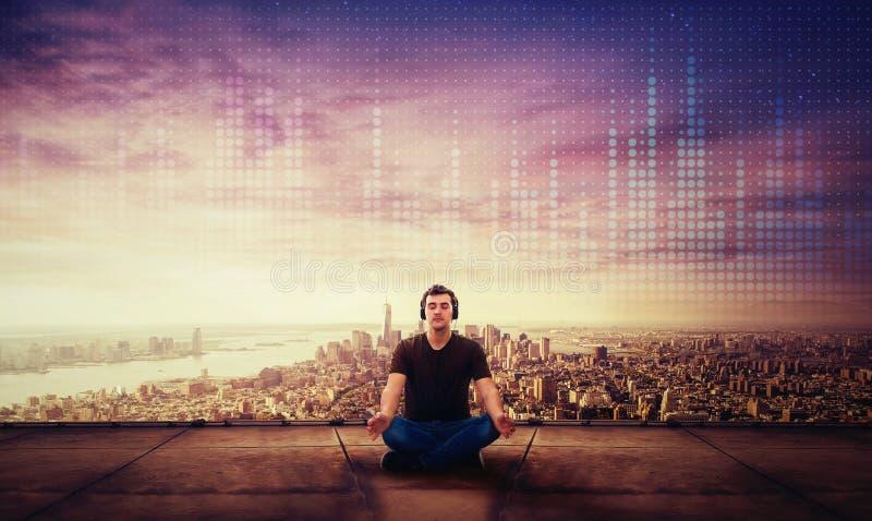 Stillhetgrabben som sitter på taket av en skyskrapa, mediterar på solnedgången över stadshorisont royaltyfria bilder