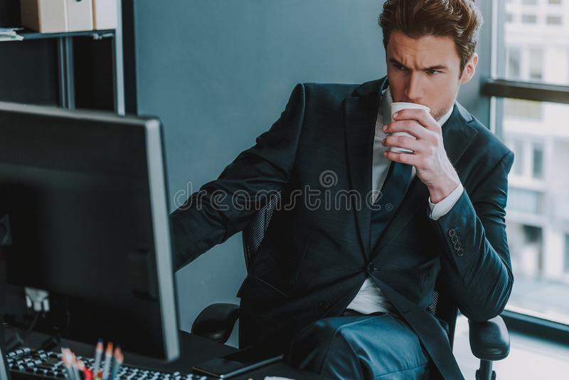 Stillhetman som ser datoren och rymmer lådakoppen royaltyfri fotografi