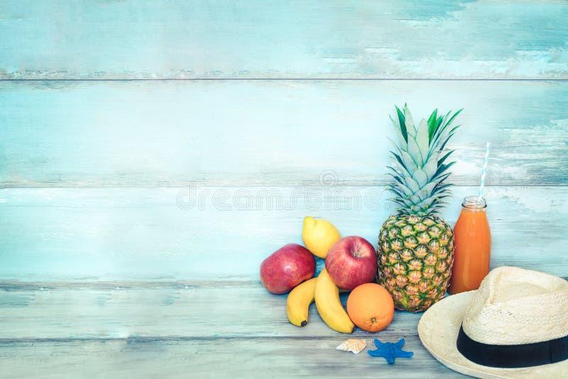 Stillife концепции лета - куча свежих фруктов, соломенной шляпы и бутылки сока multivitamin перед голубое деревенское деревянным стоковые изображения