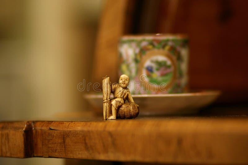 Stillife antigo asiático com netsuke do marfim e copo de chá foto de stock royalty free