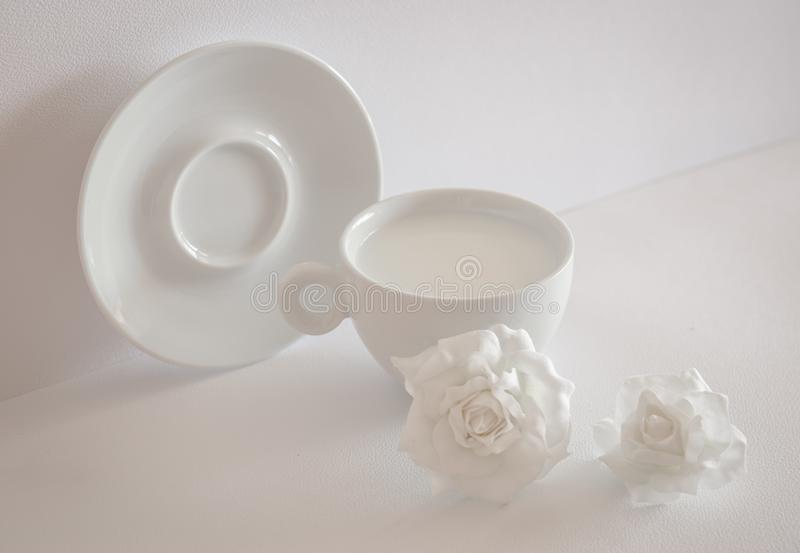 Stillife in high key. White cap with milk, plate and flowers stock photography