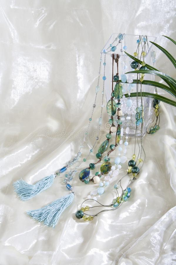 Stillife of necklace chains on white satin background. Stillife of different necklace chains on white white satin background. the colors are turquoise, blue and royalty free stock photo