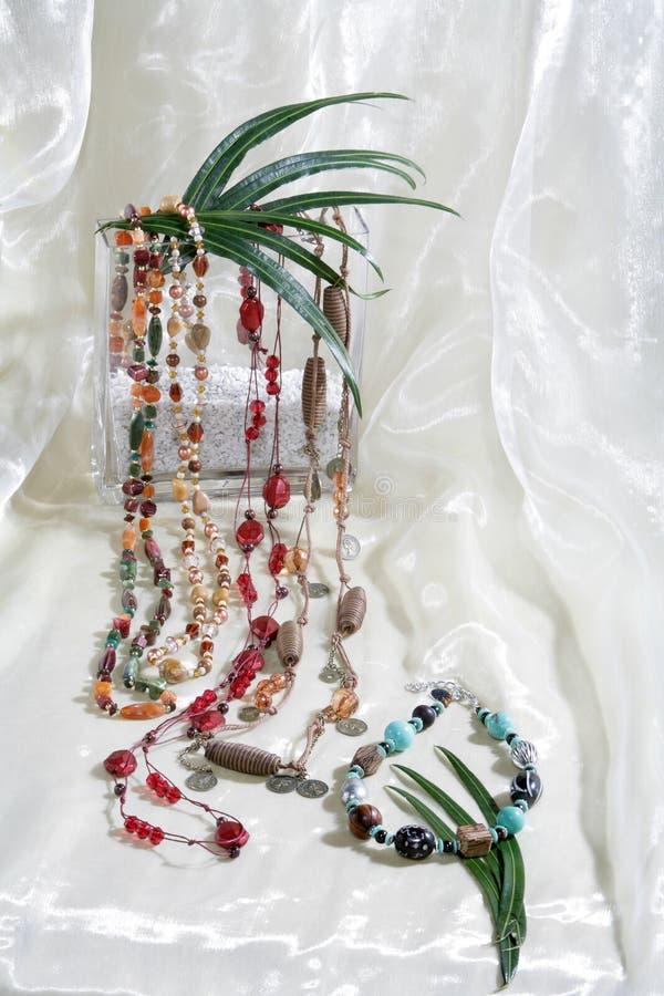 Stillife van halsbandkettingen op witte satijnachtergrond stock foto's