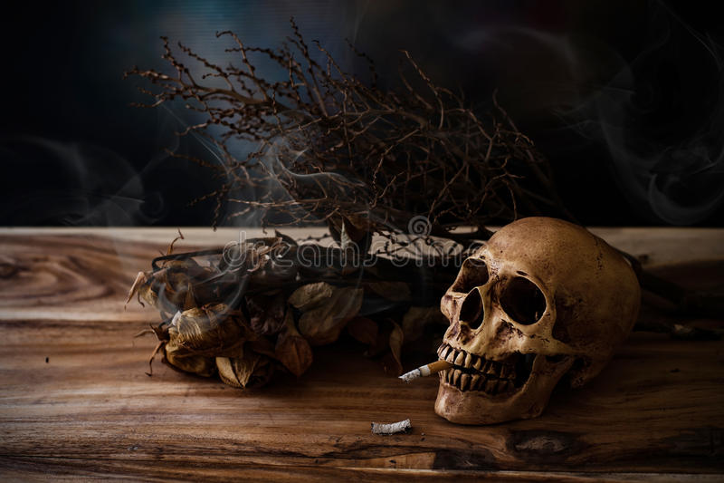 Stillleben, das menschlichen Schädel mit Zigarette auf Holztisch raucht stockbild