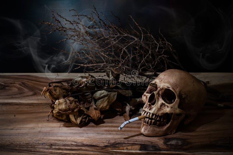 Stillleben, das menschlichen Schädel mit Zigarette auf Holztisch raucht stockfoto
