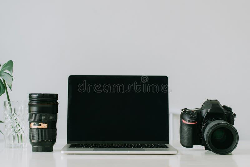 Stillleben, das zuhause vom Hauptschreibtisch mit Berufsfoto-ausr?stung, Kamera, Linse, Computermonitor, Elektronik arbeitet lizenzfreie stockfotos