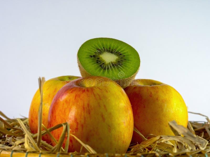 Stillleben der Kiwi und des Apfels im Korb auf weißem Hintergrund stockfotos