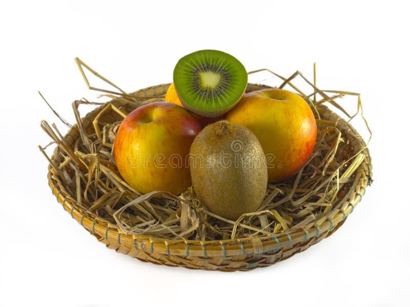 Stillleben der Kiwi und des Apfels im Korb lokalisiert auf weißem Hintergrund stockbild