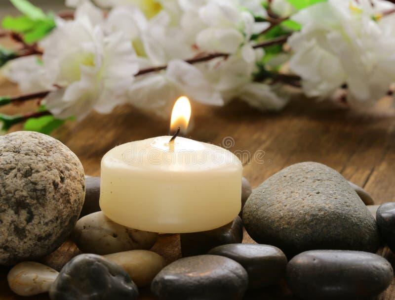 Stillleben ein brennende Kerze und Steine stockbilder