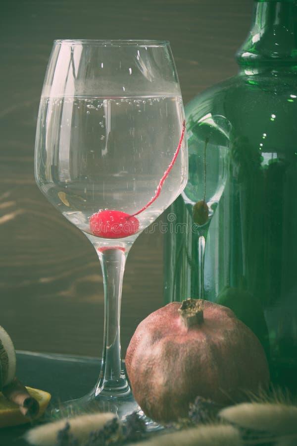 Stillleben eines Glases mit einem Cocktail mit einer Kirsche Granatapfel und grüne Flasche auf einem dunklen Hintergrund lizenzfreies stockbild