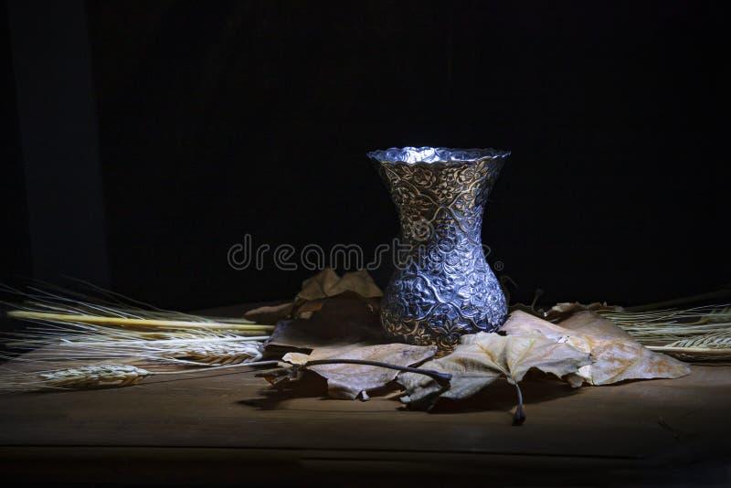 Stillleben gegen dunklen Hintergrund Metallvasenstellung auf trockenen Blättern und Stielen des Weizens stockfoto