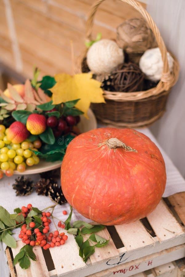 Stillleben im Herbst Kürbis, Trauben, Herbstgelb und Orangenblätter auf einer Holzkiste stockbild